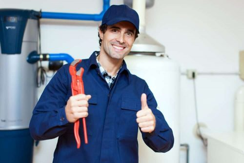 A plumber in coveralls with a water heater tank behind him