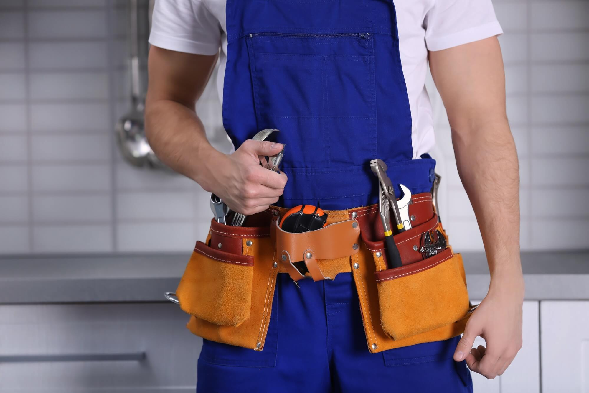 A handyman carrying tools to install and repair water heaters